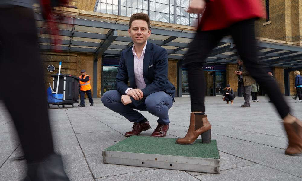 Designer Laurence Kemball-Cook with his Pavegen tile that is designed to convert the kinetic energy generated from peole stepping on it, to electical energy - perfect for areas with lots of human traffic such as railway and airport terminals. King's Cross, London. 25/11/14
