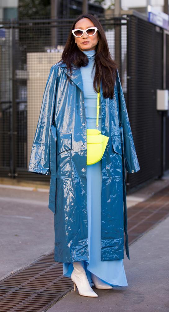 Elizabeth von der Goltz wearing a light blue long dress, white boots, neon green bag and blue vinyl coat, in Paris