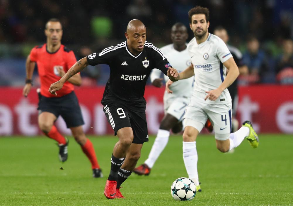 Dino Ndlovu of Qarabag FK and Cesc Fabregas of Chelsea battle for posession.