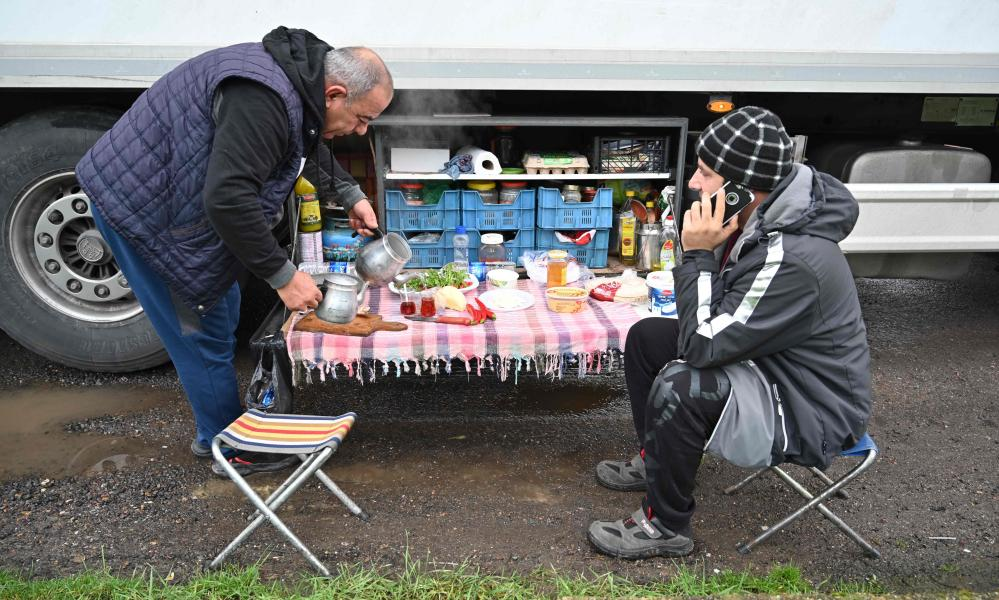 Turkish long-haul truck drivers sit down to breakfast at a truck stop off the M20 motorway