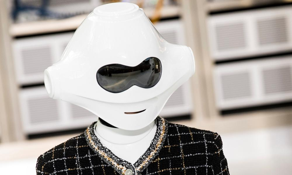 A Chanel model wearing a white plastic robot mask