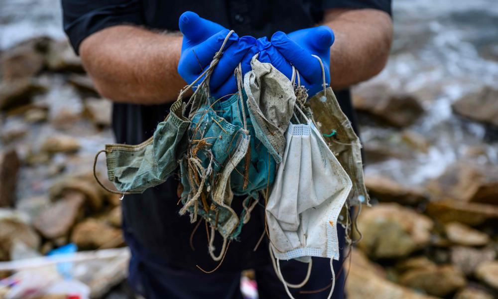 Gary Stokes, founder of the environmental group OceansAsia, shows discarded face masks he found on a beach in Hong Kong.