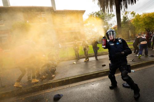 A member of Victoria police releases pepper spray during a Say No To Racism rally in Coburg