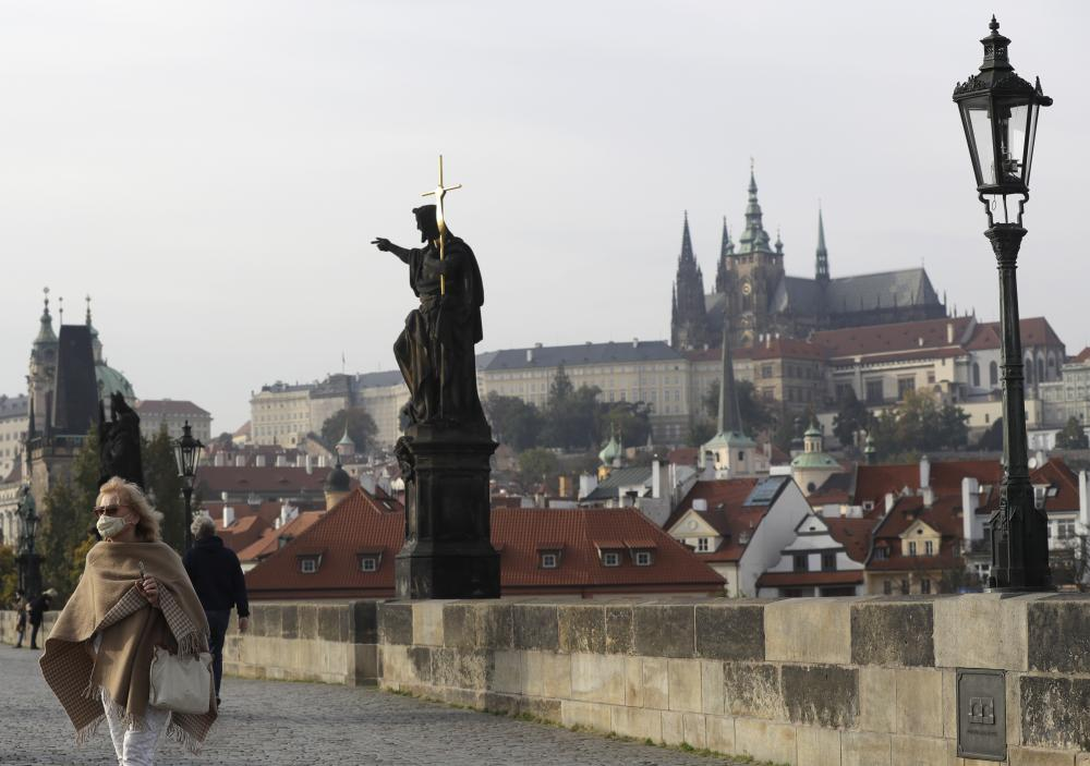 A woman wearing a face mask walks across the Charles Bridge in Prague on Wednesday.