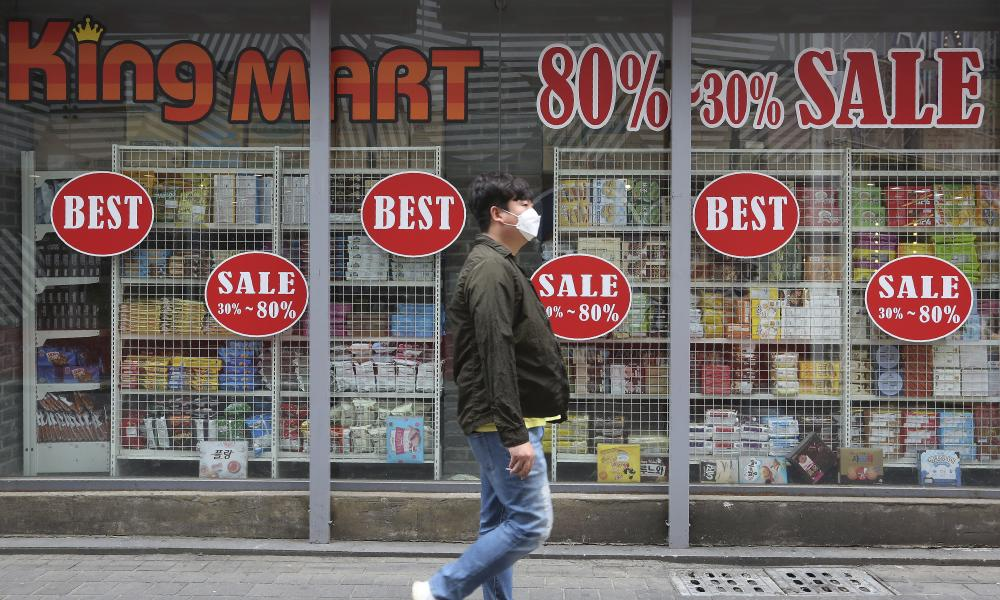 A man wearing a face mask walks by sale signs at a shopping district in Seoul, South Korea.