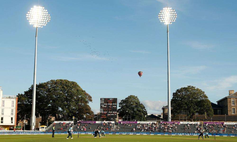 Aa hot air balloon passes behind the stadium.