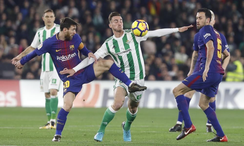 Barcelona's Messi, left, and Betis' Fabian, centre, fight for the ball.