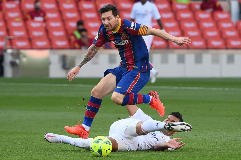 Lionel Messi hurdles Casemiro's lunge.