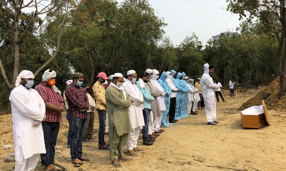 Mourners in personal protective gear offer prayers before the burial of their relative who died of Covid-19 at a cemetery in New Delhi, India