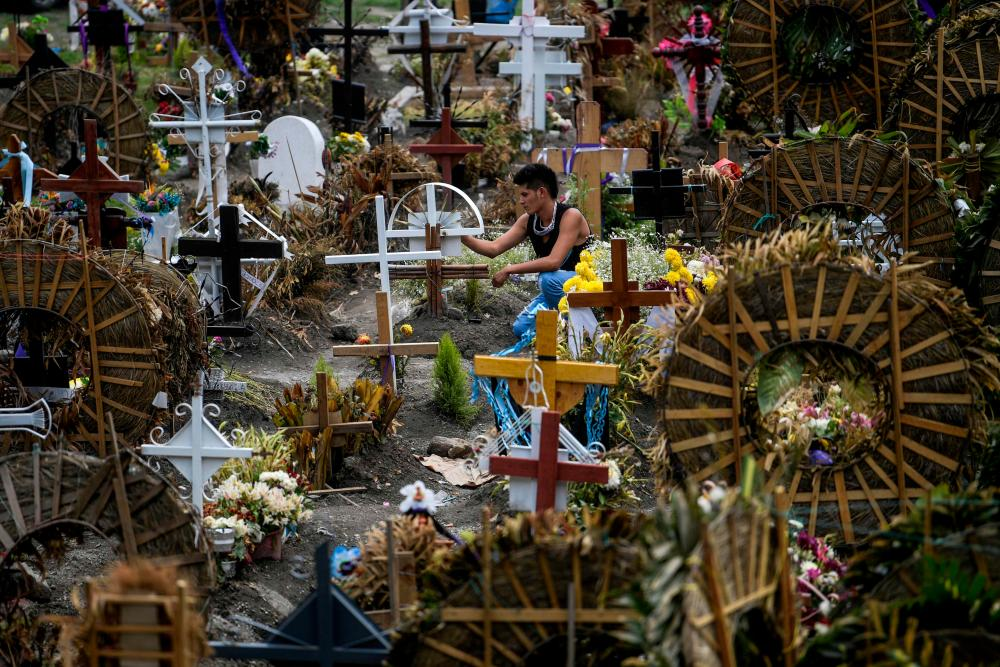 A man visits a grave at the Municipal Pantheon in Valle de Chalco, Mexico state.