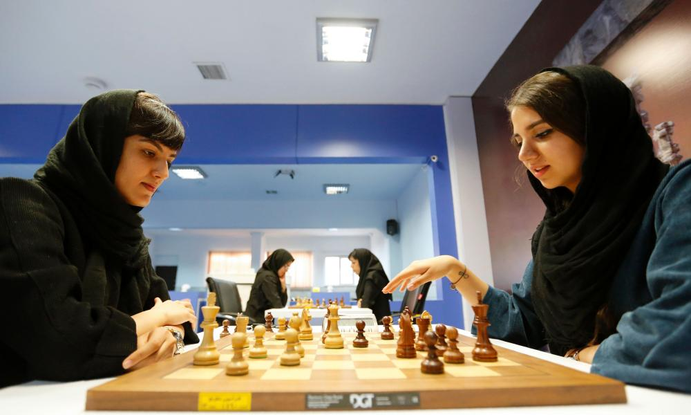 Iranian players Mitra Hejazipour, left, and Sara Khademalsharieh play at the Chess Federation in the capital Tehran, which will host the Women's World Championship.