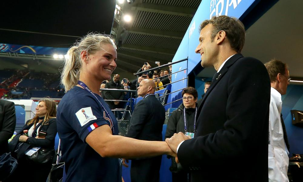 Amandine Henry, captain of the France team, talks to Emmanuel Macron, the country's president, after the opening game of the tournament against South Korea