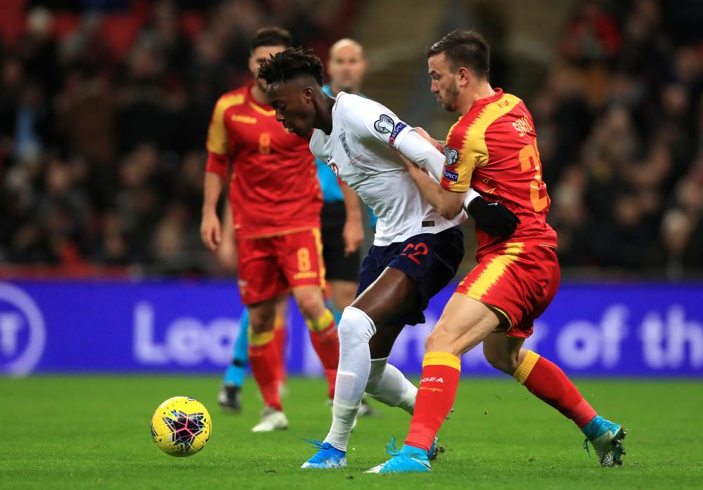 England's Tammy Abraham (left) and Montenegro's Marko Simic battle for the ball.