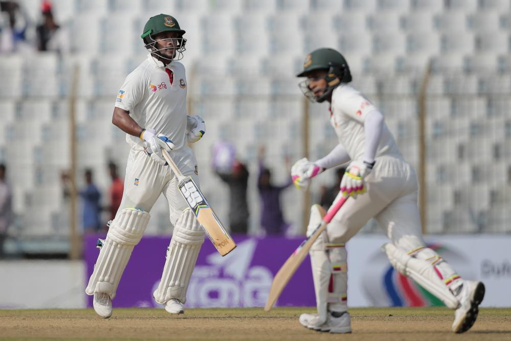 Bangladesh's captain Mushfiqur Rahim, right, and teammate Sabbir Rahman runs between the wickets during the first day of their second test cricket match against Australia in Chittagong, Bangladesh.