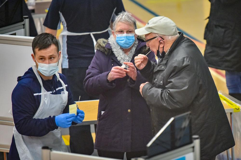 People use a test swab to take a lateral flow Covid test at Rhydycar leisure centre in Merthyr Tydfil.