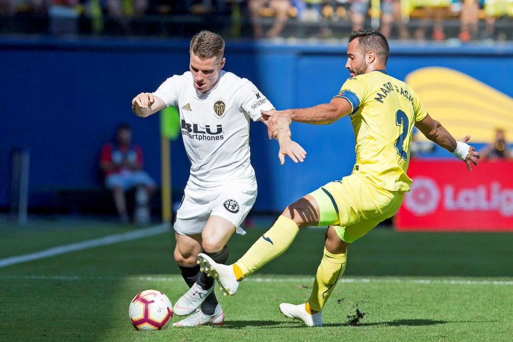 Kevin Gameiro takes on Villarreal's Mario Gaspar in the afternoon heat.