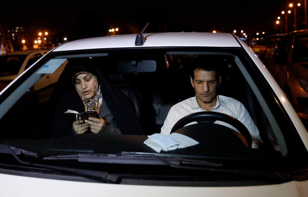A woman reads the Koran while taking part in a Ramadan service in a parking area of Tehran's Eram park