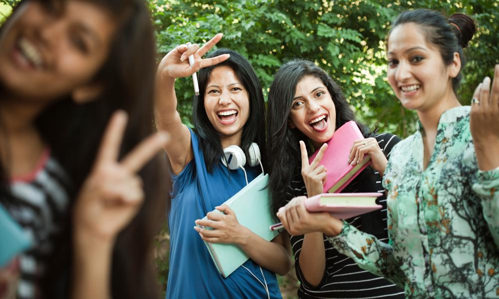 a group of young female indian students smiling and making the peace sign