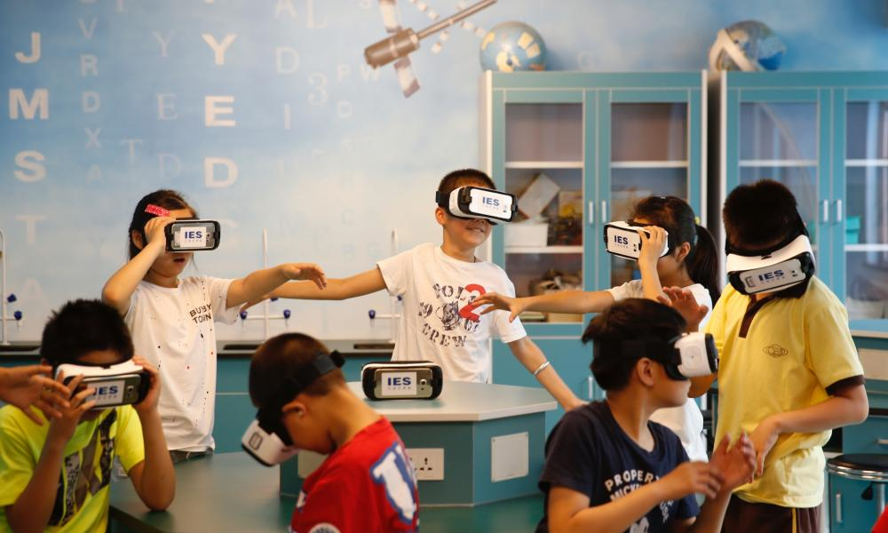 Students wear virtual reality glasses during the astronomy class in Beijing, Čína.