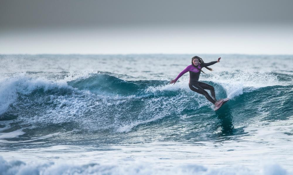 A female surfer at Fistral in Newquay in Cornwall.