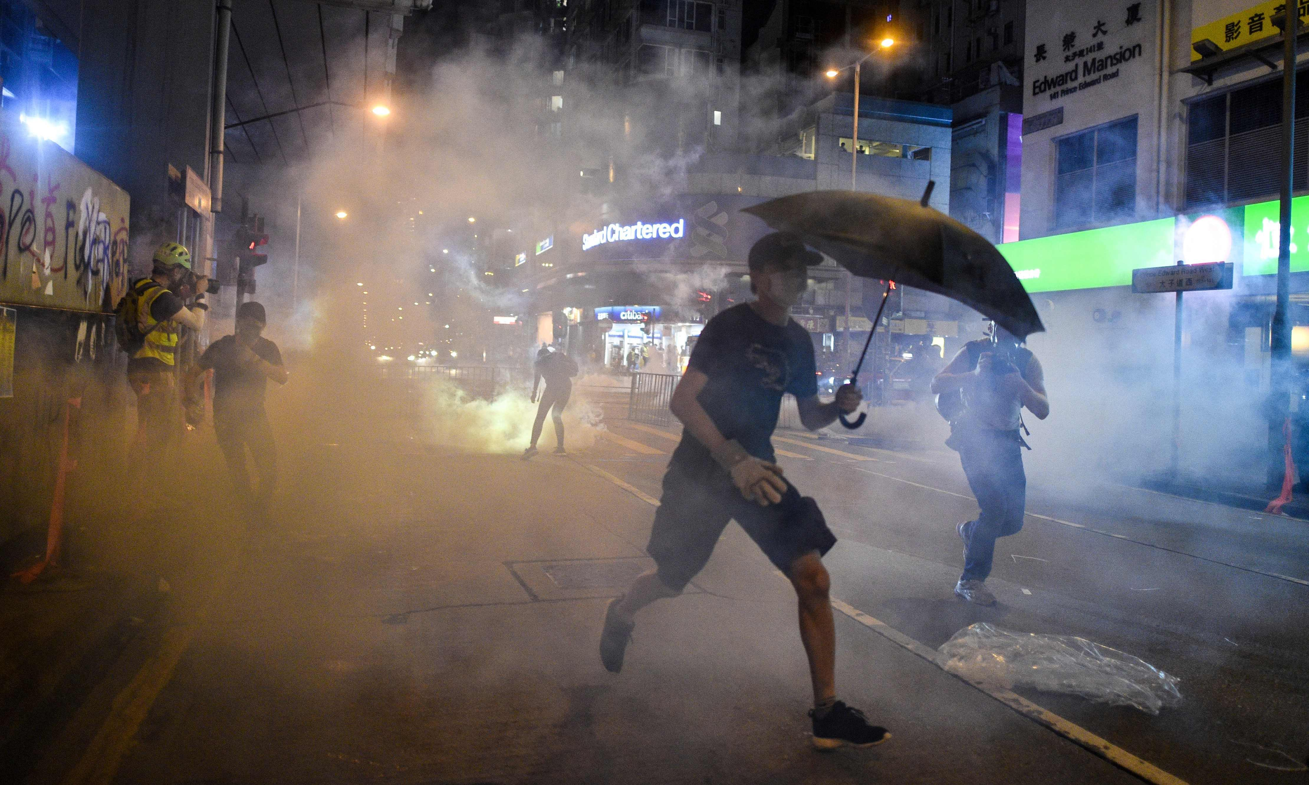 Hong Kong: Clashes as first charges brought under face mask ban law