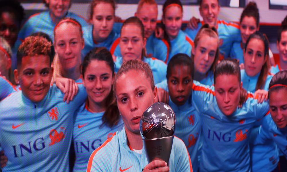Lieke Martens, backed by the Holland squad, holds the Fifa women's player-of-the-year trophy.
