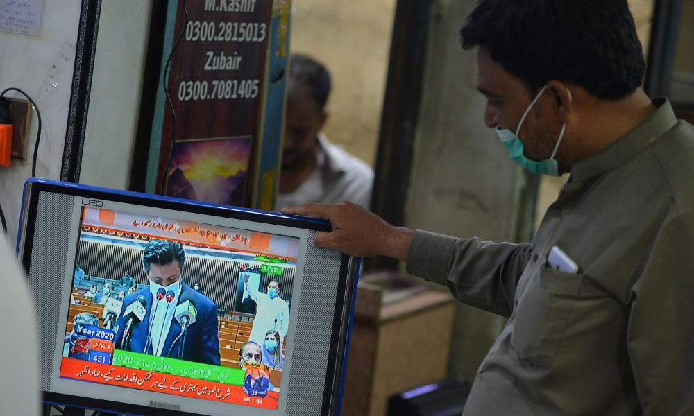 A man watches a live broadcast of Hammad Azhar's budget speech at a market in Karachi.