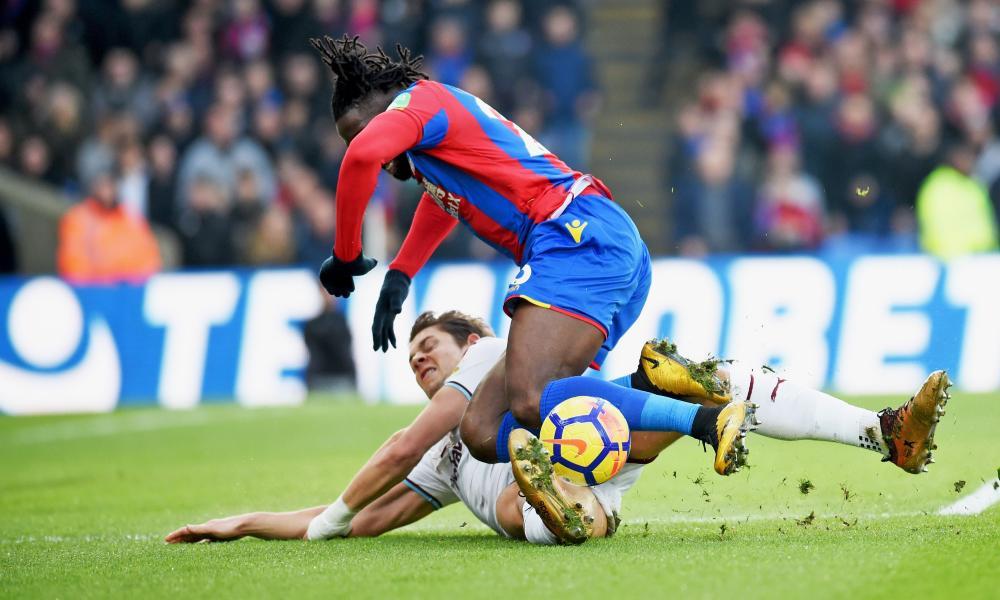 Bakary Sako of Crystal Palace is tackled by James Tarkowski of Burnley.