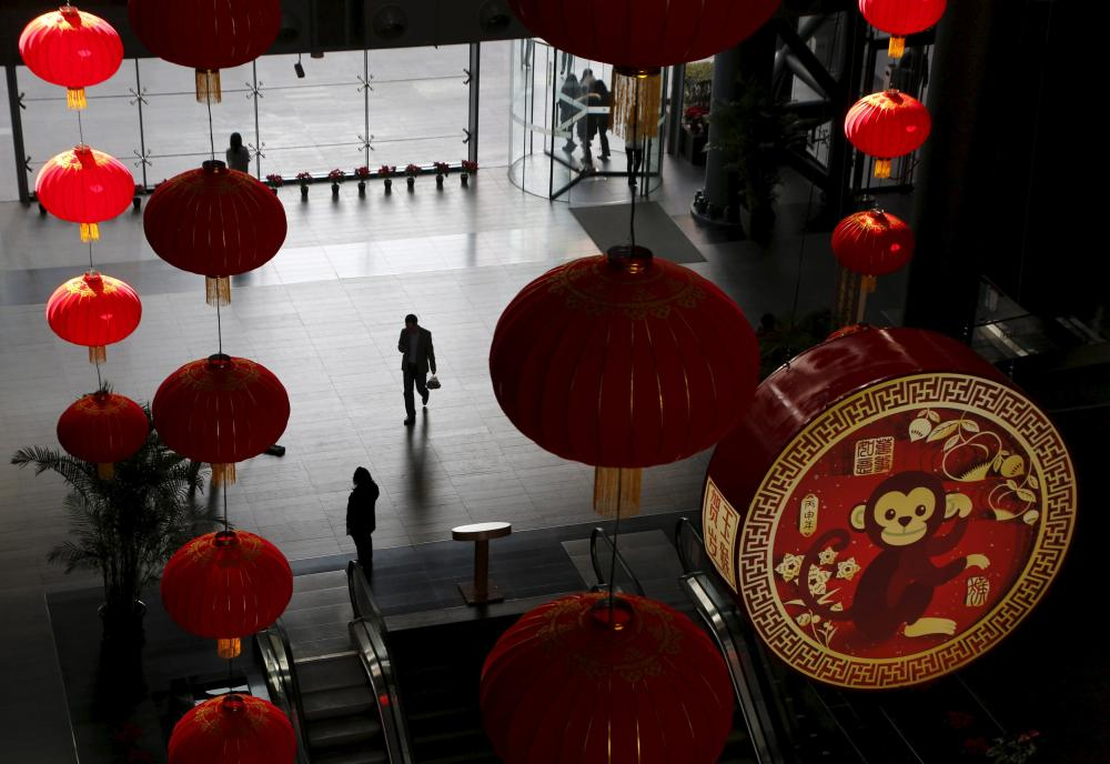 Large traditional lanterns and a sign of celebrating the upcoming new year of the Monkey at a commercial building in Beijing today.