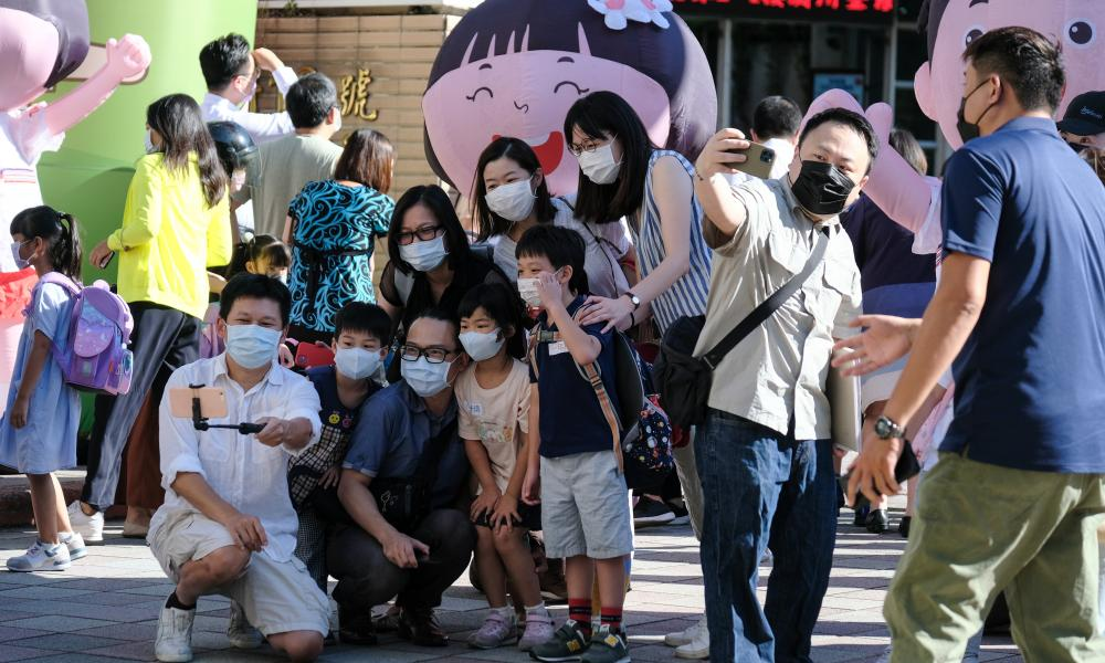 Parents and kids pose at school's garden on the first day of school amid coronavirus measures in Taipei, Taiwan.