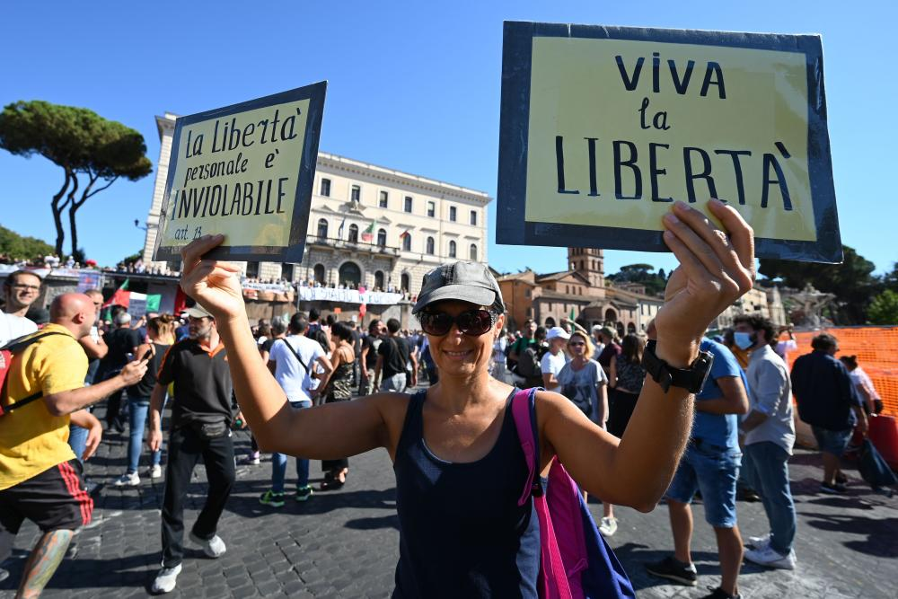 A woman holds placards reading 'Personal freedom is inviolable' and 'Long live freedom' as protesters from 'No Mask' movements, Covid-19 deniers, anti-5G movements and anti-vaxxers protest against the government's health policy on 5 September 2020 in Rome, Italy.