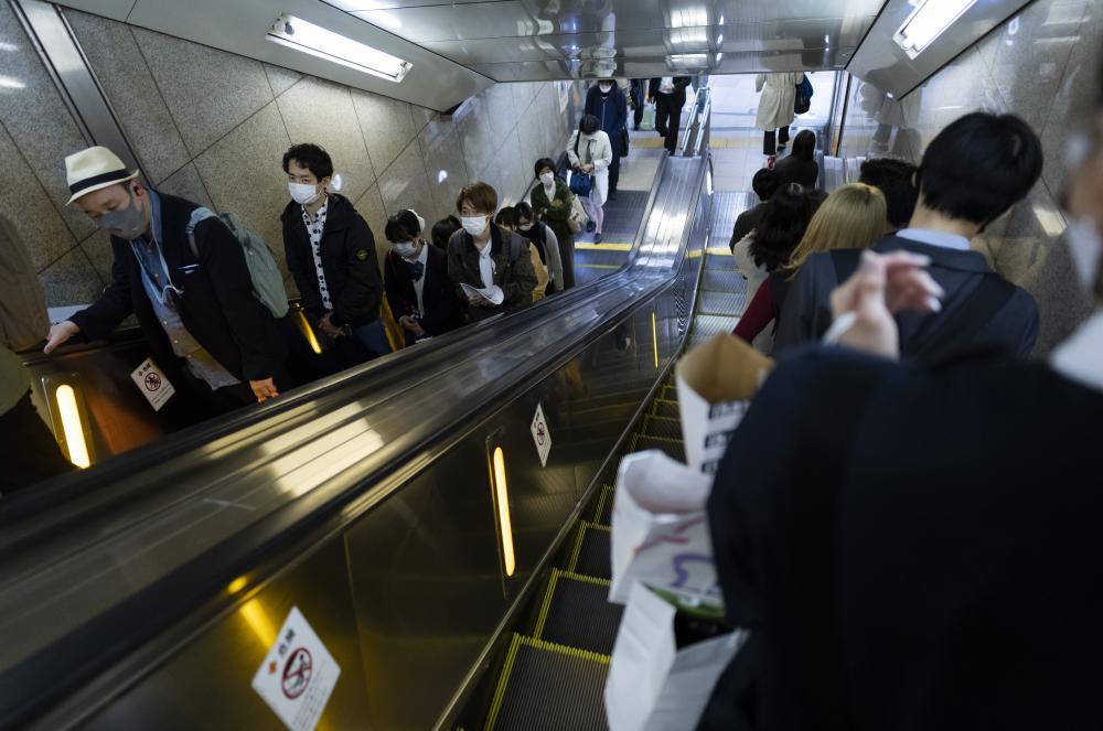 People wearing face masks walk near a train station in Osaka, western Japan, Wednesday, 14 April, 2021.