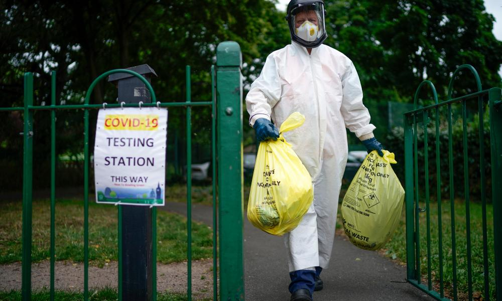 A city council worker carries rubbish from a coronavirus testing centre at Spinney Park which will be incinerated on 29 June 2020 in Leicester, England.
