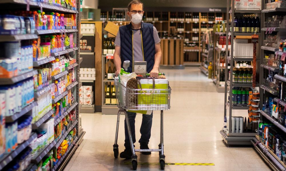 A shopper wearing a face mask in a supermarket in east London as face coverings become mandatory in shops and supermarkets in England.