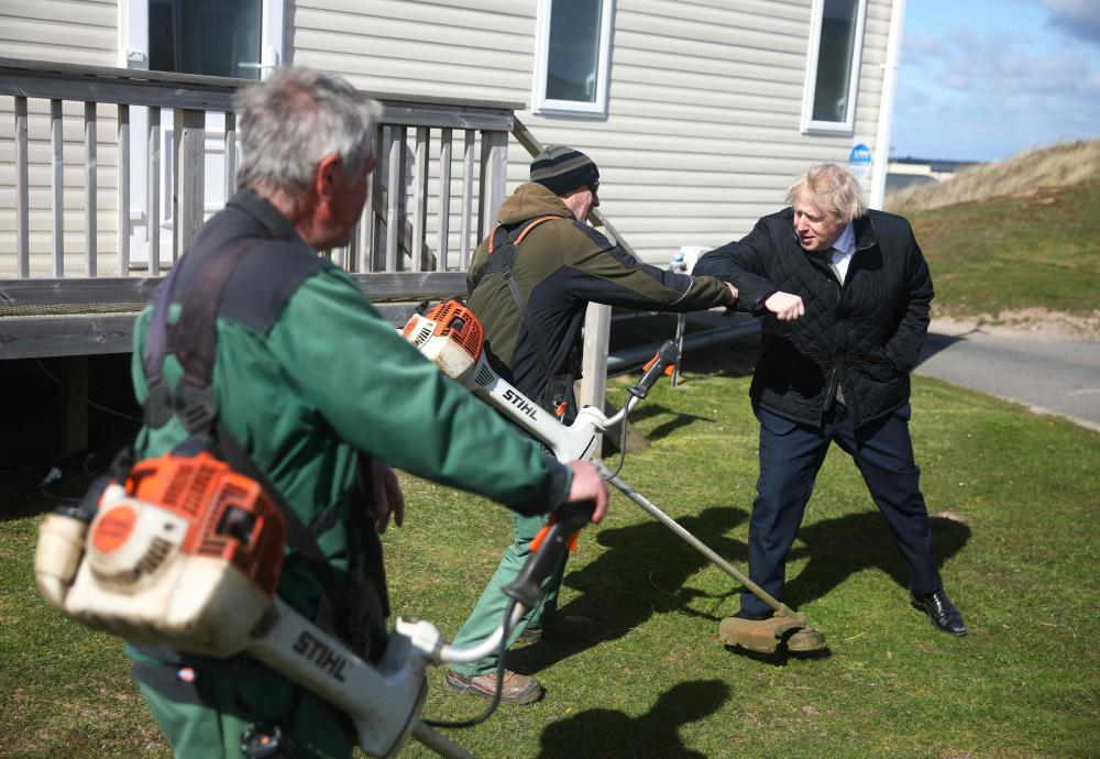 Three men in a park, one in a suit, another one with professional-looking gardening equipment.