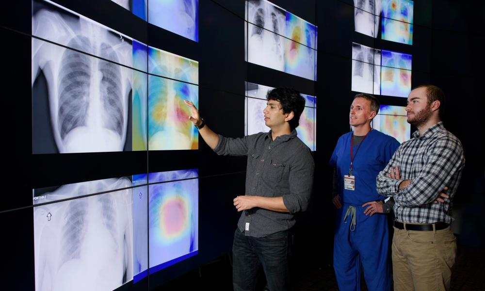 Graduate students Pranav Rajpurkar, left, and Jeremy Irvin, right, meet with radiologist Matt Lungren, MD, to discuss the results of tests using the algorithm the students developed.
