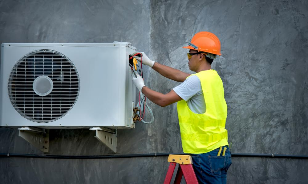 Worker Repairing Air Conditioner