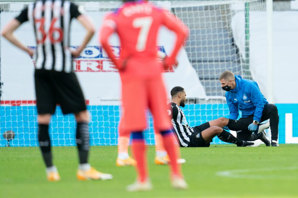 Newcastle's Jamaal Lascelles gets his leg checked out by the team doctor.