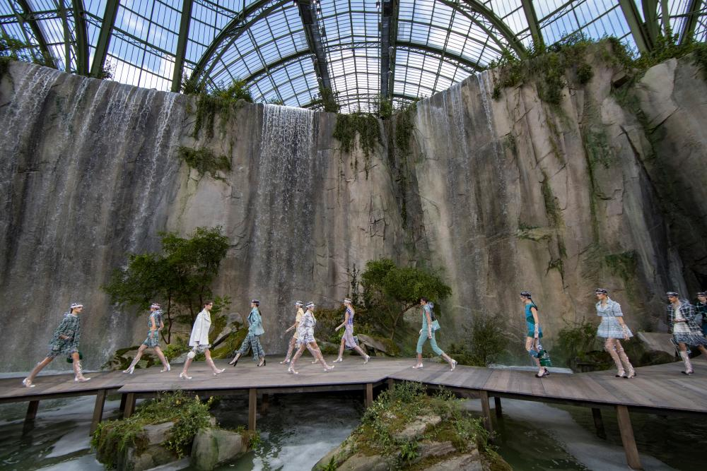 Models walk past six waterfalls cascaded under a boardwalk catwalk.