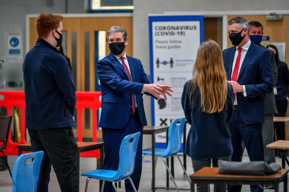 Sir Keir Starmer (second from left) speaking to students during a visit to the City College Plymouth Institute of Technology with Luke Pollard MP (right).