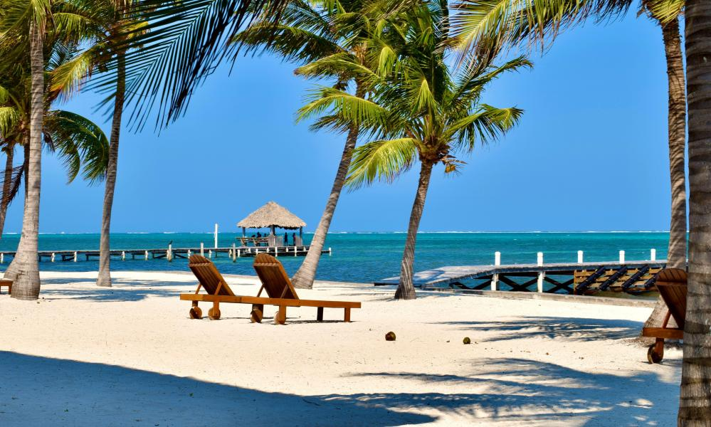 A relaxing, sunny day on a white sand beach with piers and lounge chairs in San Pedro, Belize