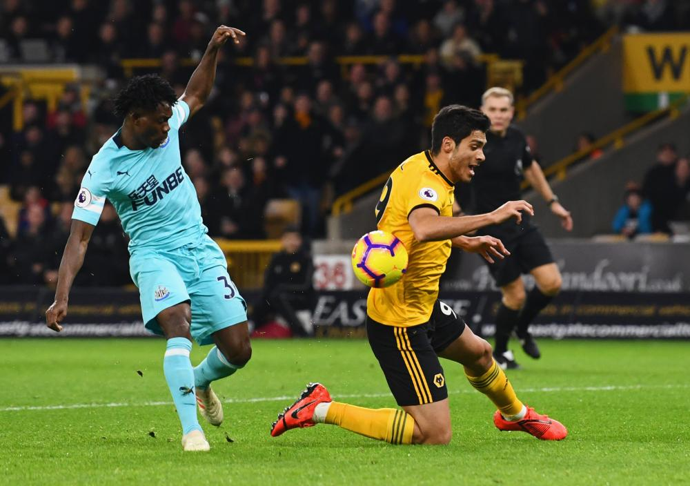 Raul Jimenez goes down in the box after a challenge by Christian Atsu.