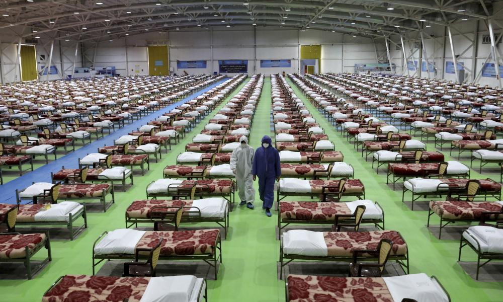 People in protective clothing walk past rows of beds at a temporary 2,000-bed hospital for COVID-19 coronavirus patients set up by the Iranian army at the international exhibition centre in northern Tehran.