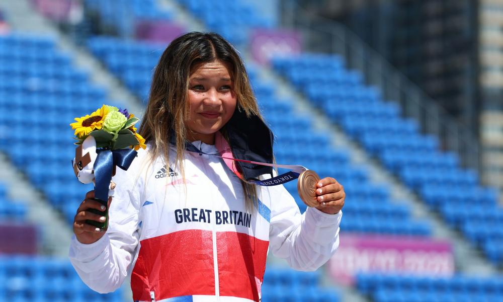 Sky Brown in Team GB tracksuit holds up the bronze medal around her neck for the cameras