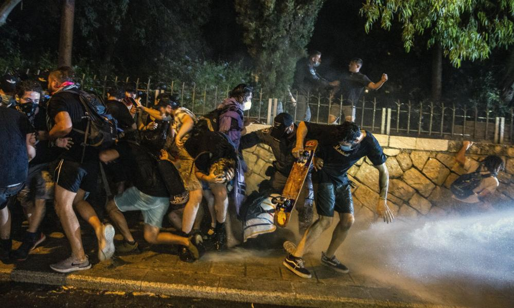 Israeli Police use a water cannon to disperse demonstrators during a protest against Israel's prime minister Benjamin Netanyahu outside his residence in Jerusalem, on Friday.