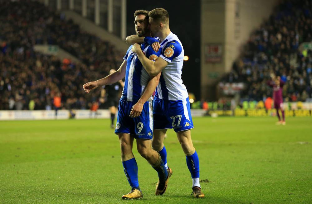 Will Grigg celebrates with Ryan Colclough.