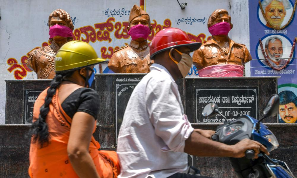 Motorists ride past the statues of Indian freedom fighter Subhas Chandra Bose (C), and actors in the Kannada cinema, Dr. Rajkumar (L) and Vishnuvardhan, wearing shawls on the face as protection against coronavirus, in Bangalore on 9 April 2020.