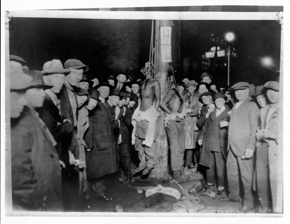 A crowd surrounds two African American men hanging from nooses on a pole.