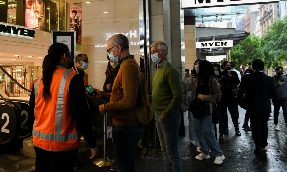 Retail staff check shoppers in to their store in Pitt Street Mall, Sydney, Australia