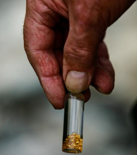 Hand holding tiny jar with panned bits of gold in it